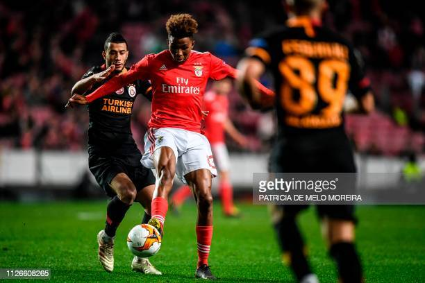 Galatasaray's Moroccan midfielder Belhanda vies for the ball with Benfica's midfielder Gedson Fernandes during the UEFA Europa League round of 32...