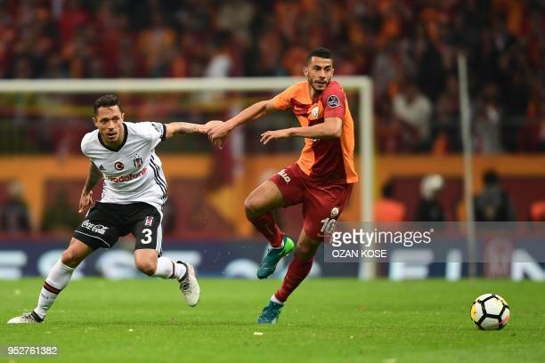 Galatasaray's Moroccan midfielder Younes Belhanda vies for the ball with Besiktas' Brazilian defender Adriano during the Turkish Spor Toto Super...