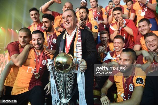 Galatasaray's players and head coach Fatih Terim pose with their trophy as they celebrate their 20172018 Turkish league champion title during a...