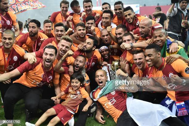 Galatasaray's players celebrate their 2017-2018 Turkish league champion title during a trophy cerenomy a day after the Turkish Spor Toto Super league...