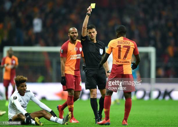Galatasaray's Senegalese midfielder Papa Alioune Ndiaye receives a yellow card as Benfica's Portuguese midfielder Gedson Fernandes sits on the pitch...