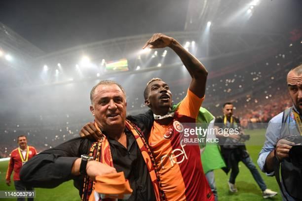 Galatasaray's Turkish head coach Fatih Terim and Galatsaray's Nigerian forward Henry Onyekuru celebrate their Turkish championship title after...