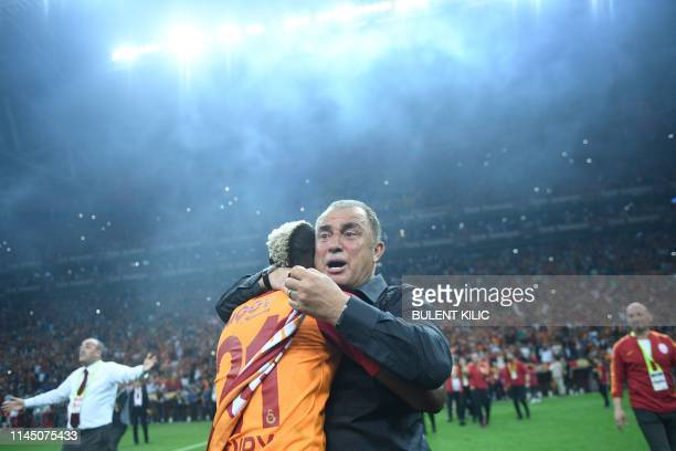 Galatasaray's Turkish head coach Fatih Terim and Nigerian forward Henry Onyekuru celebrate their Turkish championship title after winning the Turkish...