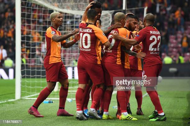 Galatasaray's Turkish midfielder Adem Buyuk is congratulated by teammates after scoring a goal during the UEFA Champions League football match...