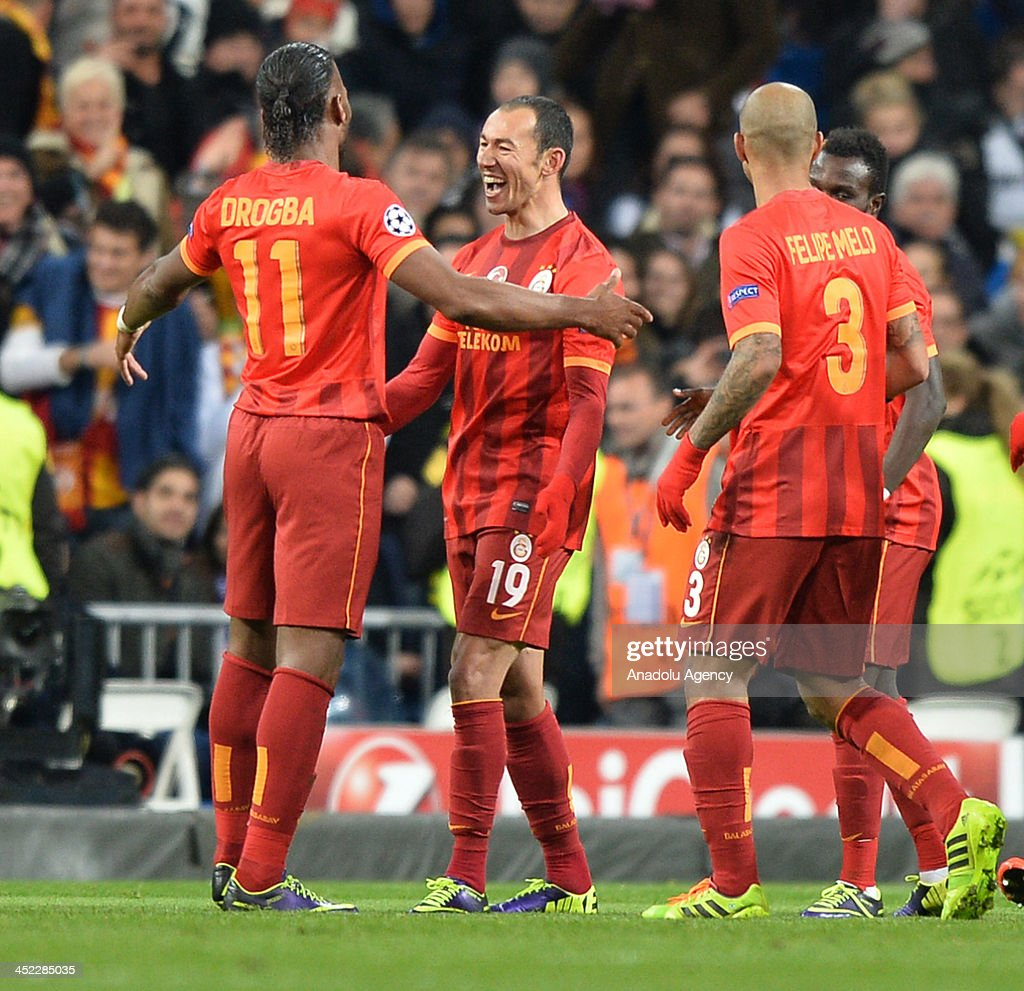 Galatasaray's Umut Bulut (C) celebrates after scoring their team first goal with Didier Drogba (L) and Felipe Melo (R) during the UEFA Champions League football match between Real Madrid vs Galatasaray at the Santiago Bernabeu Stadium on November 27, 2013 in Madrid.