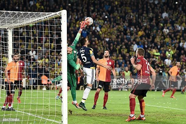 Galatasaray's Uruguayan goalkeeper Fernando Muslera stops the ball above Turkish midfielder Fenerbahce's Mehmet Topal during the Turkish Super Lig...