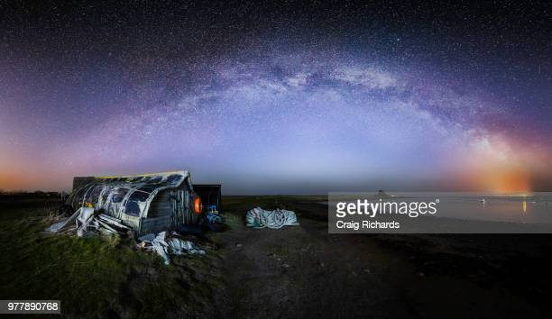 galaxy over cottage on holy island, uk - northumberland stock photos and pictures
