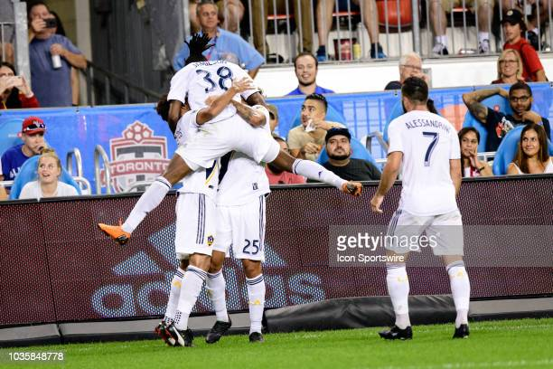 Galaxy players Jonathan dos Santos Rolf Feltscher celebrate a goal with Bradford Jamieson IV and Romain Alessandrini during the second half of the...
