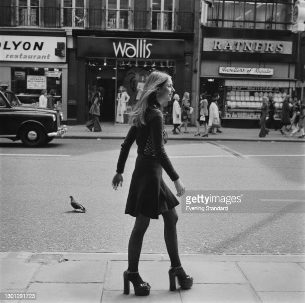 Gale Phillips wearing platform shoes on a shopping street in the UK, 3rd May 1973. In the background are Wallis and Ratners stores.
