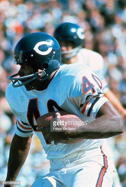 Gale Sayers of the Chicago Bears carries the ball against the Green Bay Packers during an NFL football game circa 1968 at Lambeau Field in Green Bay...