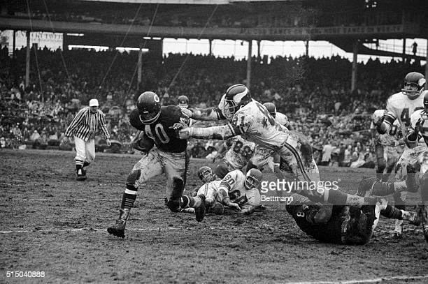 Gale Sayers of the Chicago Bears heads for a 12yard gain after escaping the outstretched arms of Minnesota Vikings defender Carl Eller