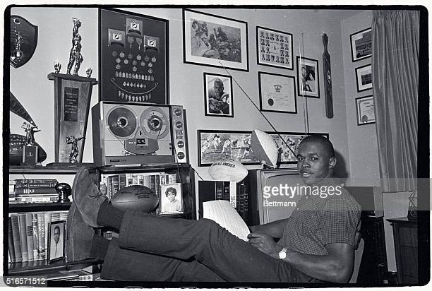 Gale Sayers rookie star of the Chicago Bears relaxes in the trophy room of his home here recently Sayers six touchdowns in the December 12th game...