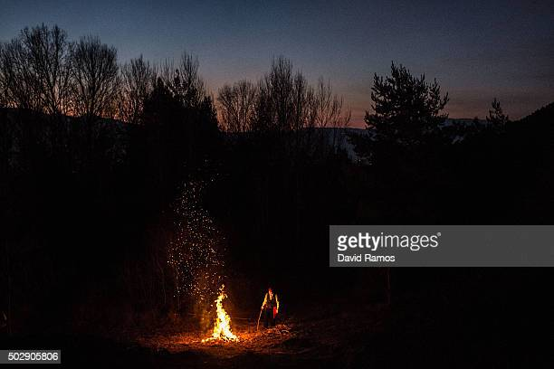 A 'Galejador' lights a bonfire in the forest during 'La Festa del Pi' in the village of Centelles on December 30 2015 in Barcelona Spain Early in the...