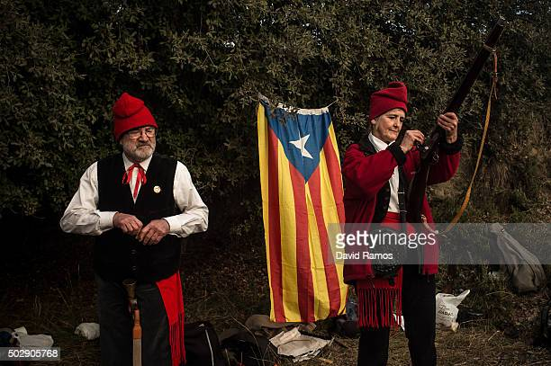 'Galejadors' load their muskets next to a proindependence Catalan flag during 'La Festa del Pi' in the village of Centelles on December 30 2015 in...