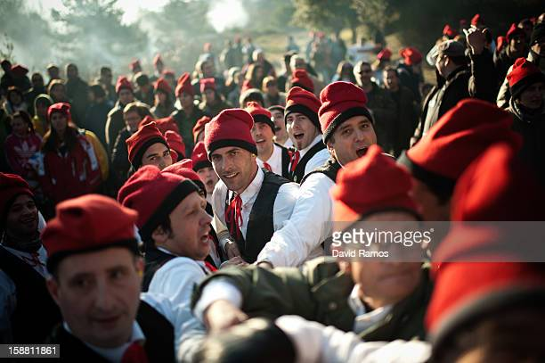 'Galejadors' pull a rope tied to the selected pine tree as it is felled during 'La Festa del Pi' in the village of Centelles on December 30 2012 in...