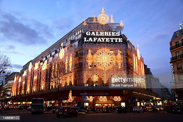 Galeries Lafayette, decorated with Christmas lights, in early evening.