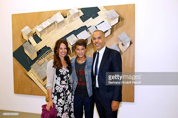 Galerist Kamel Mennour with his wife Annika and their son Kayen pose in front of at Tadashi Kawamata's Work during the 'Heroes Exhibition' to Benefit...
