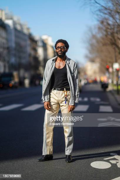 Gali Navangi wears sunglasses from Port Tanger, a vintage gray shirt, a black tank top from Armani, bi-color pants from Garoze Navangi, a belt, black...