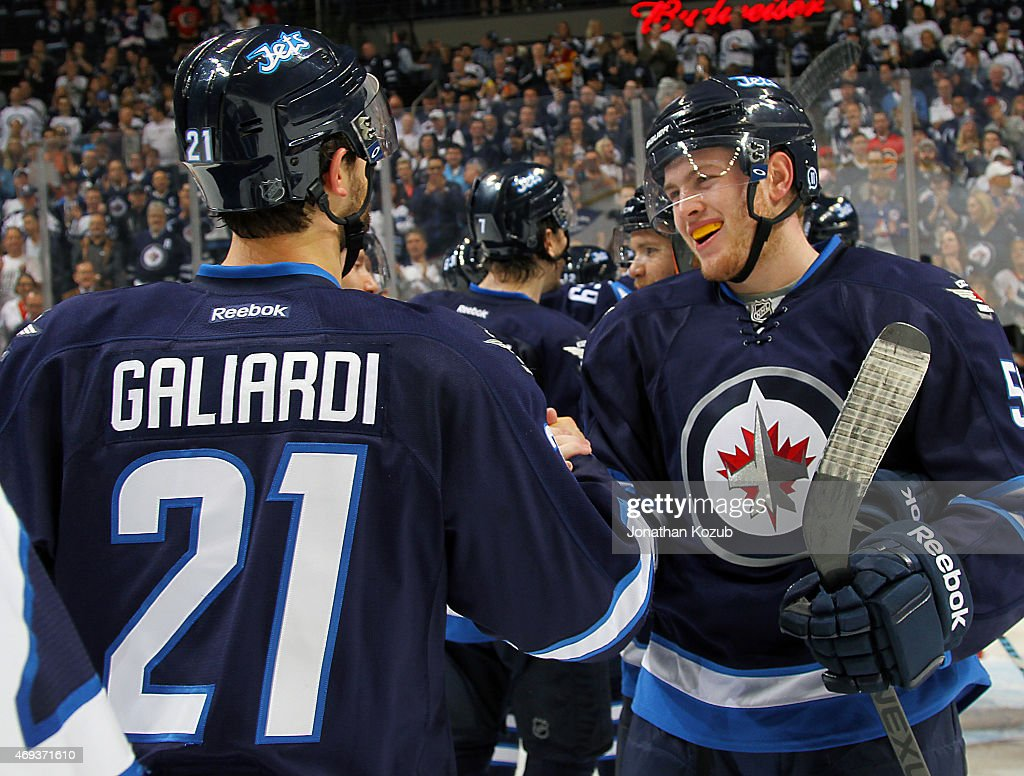 TJ Galiardi #21 and Andrew Copp #51 of the Winnipeg Jets celebrate a 5-1 victory over the Calgary Flames on April 11, 2015 at the MTS Centre in Winnipeg, Manitoba, Canada.