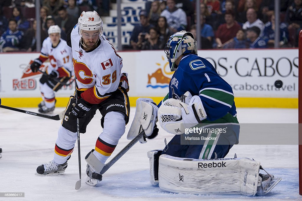 T.J. Galiardi #39 of the Calgary Flames looks for rebound on a shot on Roberto Luongo #1 of the Vancouver Canucks on January 18, 2014 at Rogers Arena in Vancouver, British Columbia, Canada.