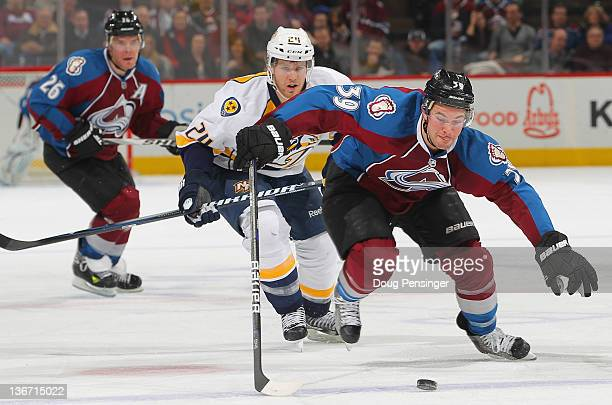 J Galiardi of the Colorado Avalanche looks to collect the puck as Matt Halischuk of the Nashville Predators and Paul Stastny of the Colorado...