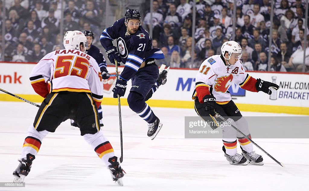 T.J. Galiardi #21 of the Winnipeg Jets goes flying behind Mikael Backlund #11 of the Calgary Flames during second period action in an NHL game at the MTS Centre on April 11, 2015 in Winnipeg, Manitoba, Canada.