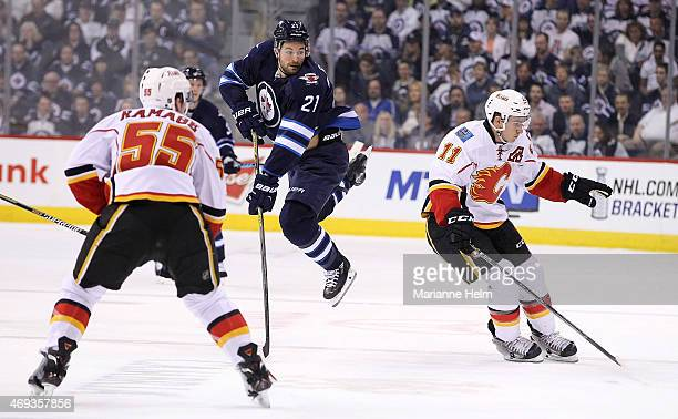 J Galiardi of the Winnipeg Jets goes flying behind Mikael Backlund of the Calgary Flames during second period action in an NHL game at the MTS Centre...