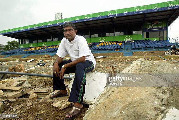 In this picture taken 05 January 2005 former Sri Lankan cricketer Jayananda Warnaweera sits on debris strewn across the cricket pitch at The Galle...