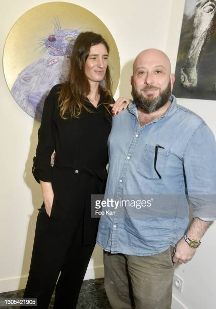 """Gallerist Marguerite Milin and curator /painter Marc Molk pose with Molk's work during """"Ils Ont Dit Oui"""" Exhibition an Amalteo Institute Project..."""