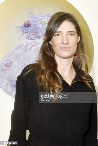 """Gallerist Marguerite Milin poses with a work during """"Ils Ont Dit Oui"""" Exhibition an Amalteo Institute Project Curated by Marc Molk at Galerie..."""