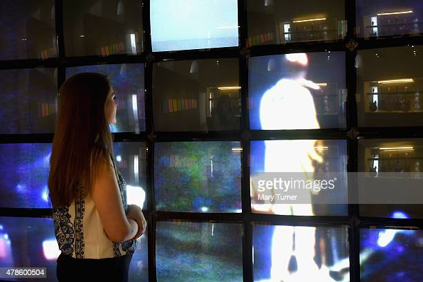 A gallery assisstant watches screens showing archive footage featured in 'The Jam About the Young Idea' at Somerset House on June 25th 2015 in London...