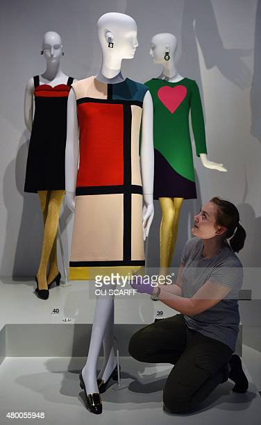 A gallery assistant adjusts a cocktail dress designed by French fashion designer Yves Saint Laurent during a photocall at the Bowes Museum in Barnard...
