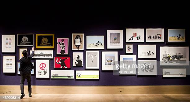 Gallery assistant adjusts a picture in a collection of 30 Banksy prints owned by the British gallery owner, Steve Lazarides, at Bonhams auction house...