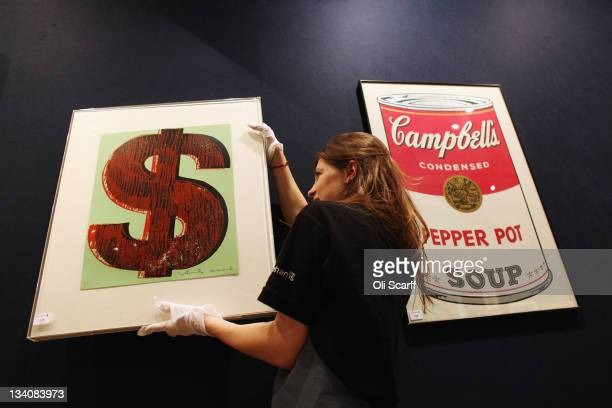 A gallery assistant adjusts a print of an Andy Warhol artwork estimated to fetch 20000 GBP in Bonhams auction house on November 25 2011 in London...