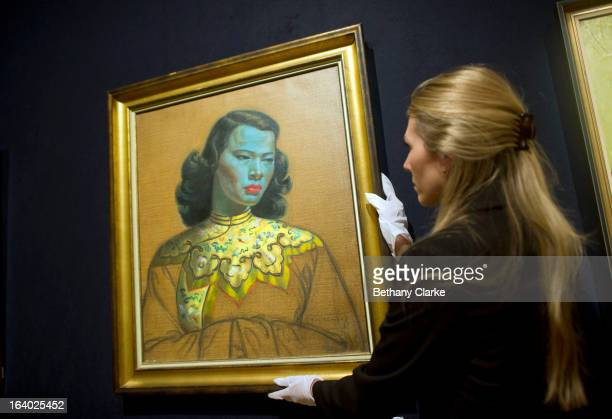 """Gallery assistant at Bonhams adjusts """"Chinese Girl"""" by Tretchikoff on March 19, 2013 in London, England. 'Chinese Girl' is the most iconic work by..."""