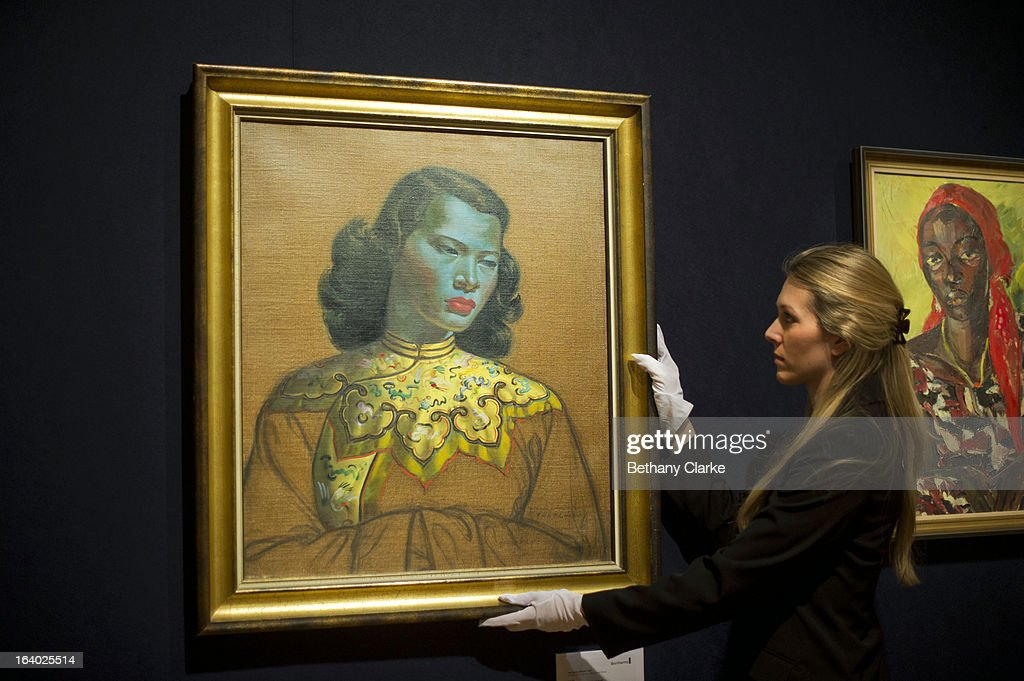 A gallery assistant at Bonhams adjusts 'Chinese Girl' by Tretchikoff on March 19, 2013 in London, England. 'Chinese Girl' is the most iconic work by Vladimir Tretchikoff and is said to be the most widely reproduced and recognisable picture in the world. The picture will be sold at Bonhams South African art sale on March 20, 2013 for an estimated 400,000 GBP.