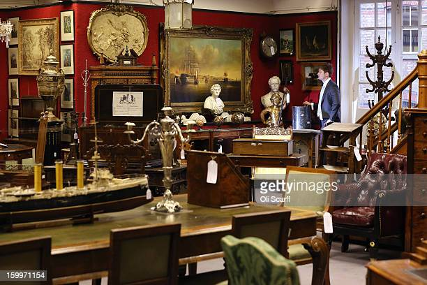 A gallery assistant at Bonhams auction house admires the lots for sale in their forthcoming 'Gentleman's Library Sale' on January 24 2013 in London...