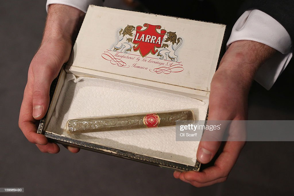 A gallery assistant at Bonhams auction house holds a Cuban cigar owned by Sir Winston Churchill, which is expected to fetch 700 GBP in their forthcoming 'Gentleman's Library Sale', on January 24, 2013 in London, England. The auction includes an eclectic mix of rare items such as a pygmy hippo skeleton and a MI9 spy catalogue. It will take place in Bonhams Knightsbridge on January 29 and 30, 2013.