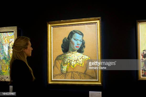 """Gallery assistant at Bonhams looks at """"Chinese Girl"""" by Tretchikoff on March 19, 2013 in London, England. 'Chinese Girl' is the most iconic work by..."""