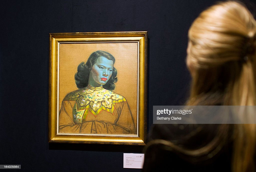 A gallery assistant at Bonhams looks at 'Chinese Girl' by Tretchikoff on March 19, 2013 in London, England. 'Chinese Girl' is the most iconic work by Vladimir Tretchikoff and is said to be the most widely reproduced and recognisable picture in the world. The picture will be sold at Bonhams South African art sale on March 20, 2013 for an estimated 400,000 GBP.