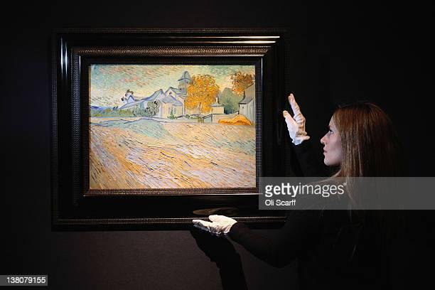 A gallery assistant at Christie's auction house adjusts a painting by Vincent Van Gogh entitled 'Vue de l'Asile de la Chapelle de SaintRemy' which...