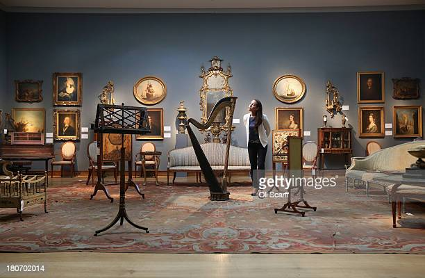 A gallery assistant at Christie's auction house admires a Regency doubleaction harp on September 16 2013 in London England The work which is expected...