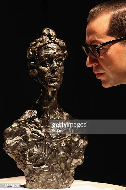 A gallery assistant at Christie's auction house admires a sculpture by Alberto Giacometti entitled 'Annette Venise' on February 2 2012 in London...