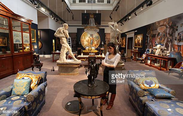 Gallery assistant at Sotheby's auction house examines a statue included in the forthcoming sale of furniture and works of art owned by Gianni...