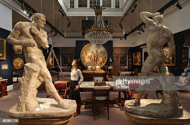 A gallery assistant at Sotheby's auction house examines one of Canova's wrestlers included in the forthcoming sale of furniture and works of art...