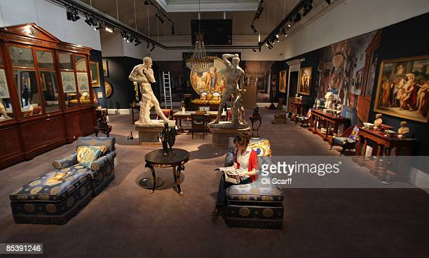 A gallery assistant at Sotheby's auction house reads a brochure for the forthcoming sale of furniture and works of art owned by Gianni Versace whilst...