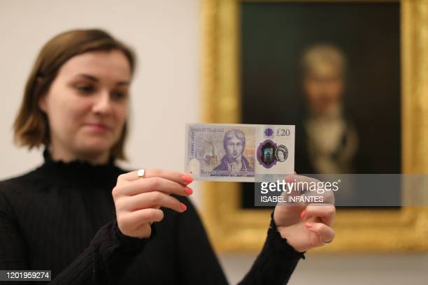 Gallery assistant displays the new twenty pound note wich features British painter JW Turner in front of Turners self-portrait, which forms part of...