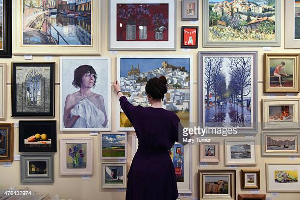Gallery Assistant Eleanor Connor straightens one of hundreds of original works of art which are displayed and sold in the 'Not the Royal Academy'...