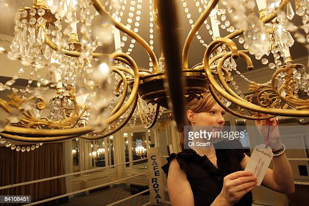 A gallery assistant for Bonhams auctioneers adjusts the guide price tag on a chandelier at the Cafe Royal on Regent Street on December 22 2008 in...