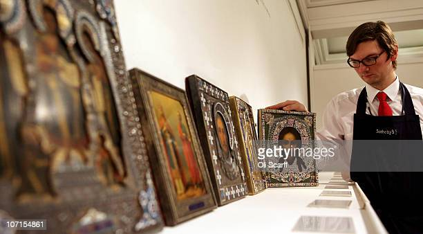 A gallery assistant for Sotheby�s auction house admires a silver and enamel icon of the Mandylion Orest Kurlyukov from Moscow made around 1899 which...